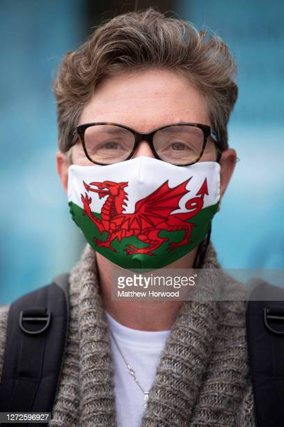 A woman poses for a photograph wearing a Wales flag face covering on September 11 2020 in Cardiff Wales In a tightening of lockdown rules intended to...