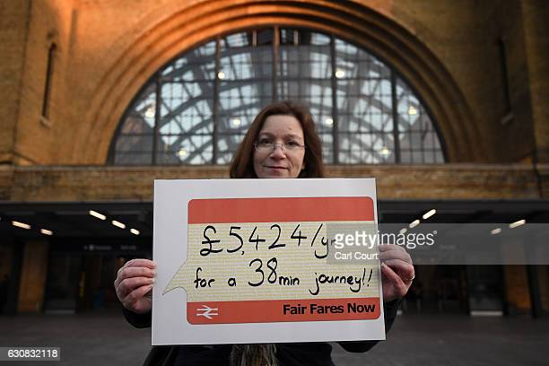 A woman poses for a photograph with a banner after taking part in a flashmob to demonstrate against rail fare increases on January 3 2017 in London...