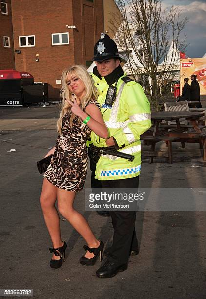 A woman poses for a photograph with a police officer while making her way towards the exit at Aintree after the second day of the annual Grand...