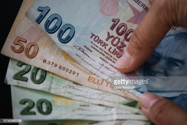 Woman poses for a photograph with Turkish Lira currency on August 13, 2018 in Istanbul, Turkey.The lira hit another record low overnight forcing...