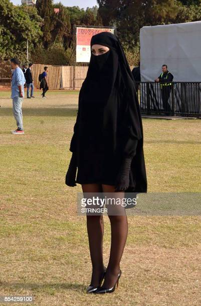 A woman poses for a picture in a niqab mini skirt and high heels during the rock festival Le Boulevard in the Moroccan city of Casablanca on...