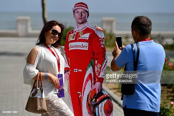 A woman poses for a picture next to a lifesize cutout of Scuderia Ferrari's Finnish driver Kimi Raikkonen on June 17 2016 in Baku two days ahead of...