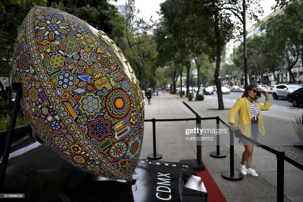 A woman poses for a picture next to a monumental American football balloon sculpture called 'Waikamete Waiwari' ('Winning') made of fiberglass and bronze plated in gold and worked in Huichol indigenous art, placed along Reforma avenue as part of an exposition called 'the world's biggest Huichol exhibit', in Mexico City, on February 8, 2018. One hundred Wixarikas indigenous artists from the social and cultural company Paricuta made 10 monumental works of art inspired by sports and nature, which were put on public display on the street. /