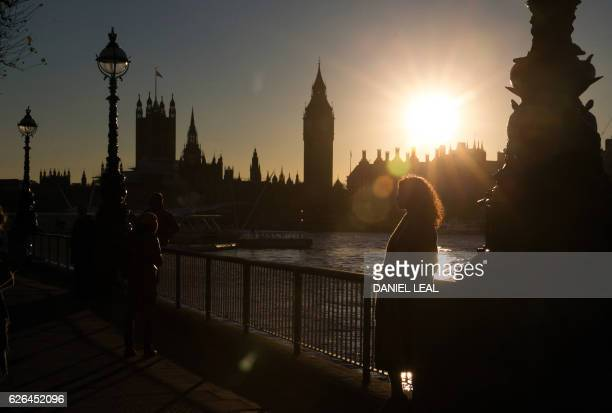 A woman poses for a pictures on the southbank of the River Thames opposite the Houses of Parliament and Big Ben in central London at sunset on...