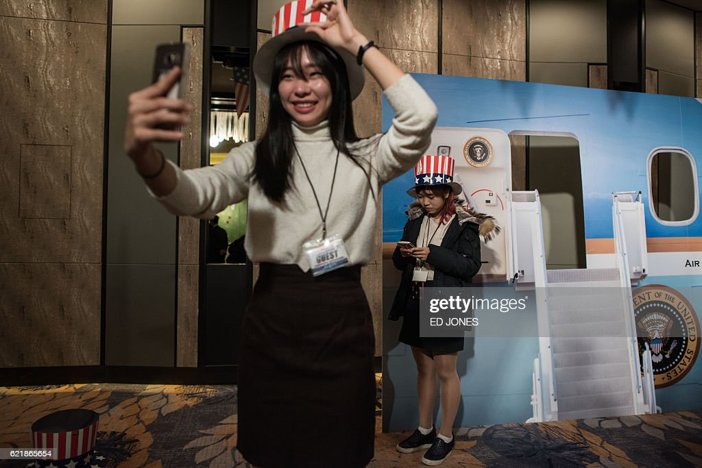 TOPSHOT - A woman poses for a selfie at an election event organised by the US embassy, at a hotel in Seoul on November 9, 2016. Donald Trump's stunning performance in the US presidential election triggered shock and angst in Asia, where observers fretted over the implications for everything from trade to human rights and climate change. / AFP / Ed JONES