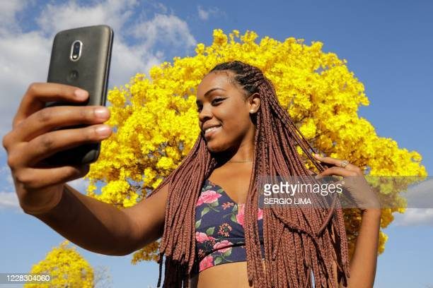 Woman poses for a selfie in front of a yellow ipe or lapacho in the central region of Brasilia on September 1, 2020.