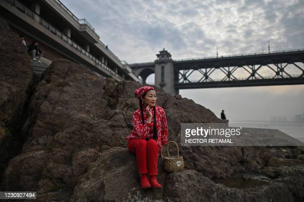 Woman poses for a selfie on her mobile phone next to the Yangtze River in Wuhan, China's central Hubei province on February 2, 2021.