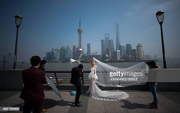 A woman poses for a wedding picture at the Bund in front of the financial district of Pudong in Shanghai on a sunny day on March 19 2015 AFP PHOTO /...