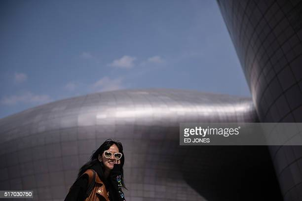 A woman poses for photographers prior to a show during Seoul fashion week at the Dongdaemun Design Plaza in Seoul on March 23 2016 Seoul fashion week...