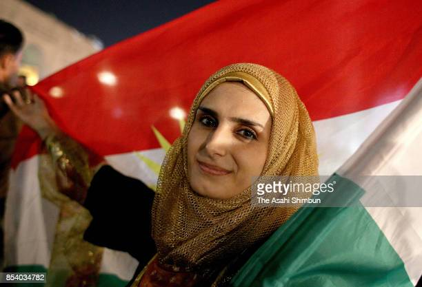 A woman poses for photographs holding the Kurdish flag after polls closed in the Kurdistan independence referendum on September 25 2017 in Erbil Iraq...
