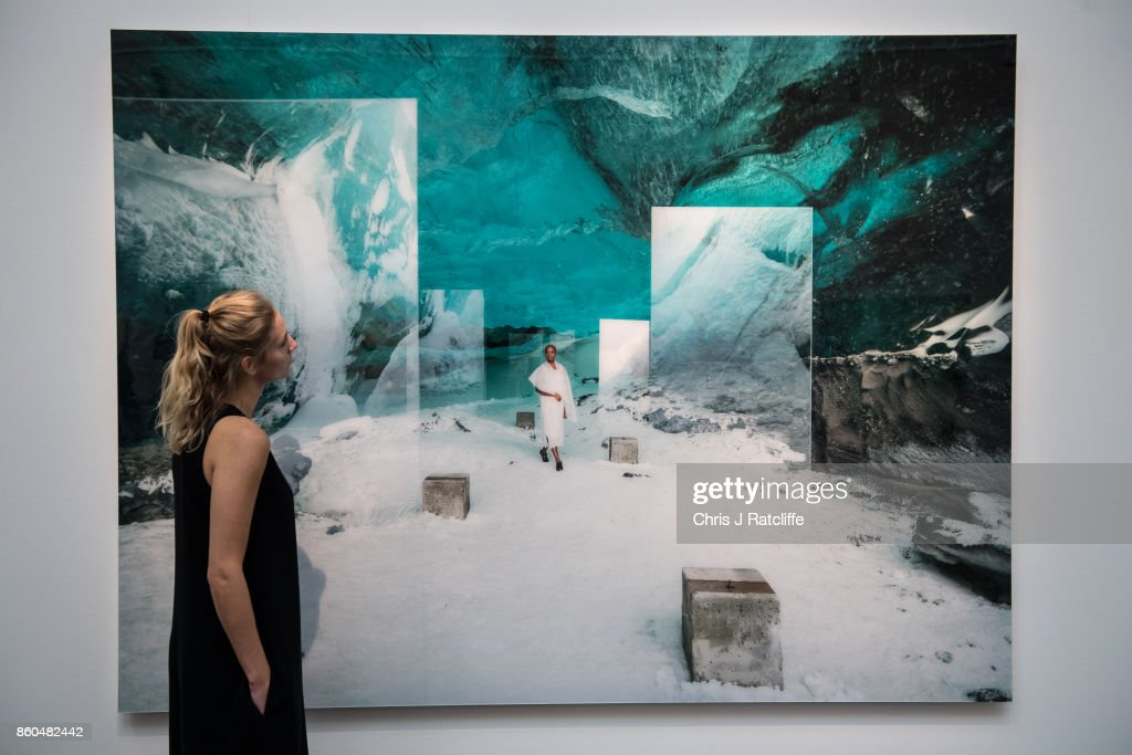 A woman poses for photographs next to En Passage by Isaac Julien, estimated at £18,000-£25,000, during an Art for Grenfell press call at Sotheby's Art for Grenfell preview on October 12, 2017 in London, United Kingdom. The 'Art for Grenfell' auction will take place on October 16 2017 and includes work by contemporary artists.