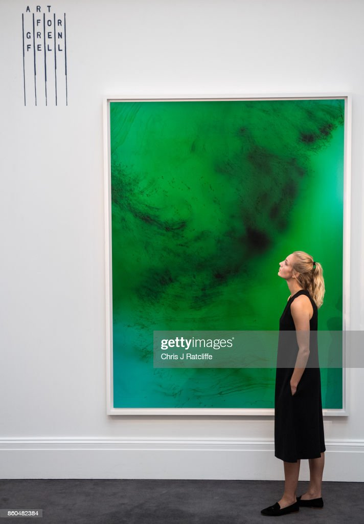 A woman poses for photographs next to Freischwimmer 193 by Wolfgang Tillmans, estimated at £120,000-£180,000, during an Art for Grenfell press call at Sotheby's Art for Grenfell preview on October 12, 2017 in London, United Kingdom. The 'Art for Grenfell' auction will take place on October 16 2017 and includes work by contemporary artists.