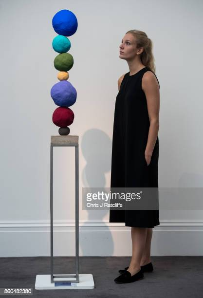 A woman poses for photographs next to Stack 7 Ultramarine Blue by Annie Morris estimated at £5000£7 during an Art for Grenfell press call at...