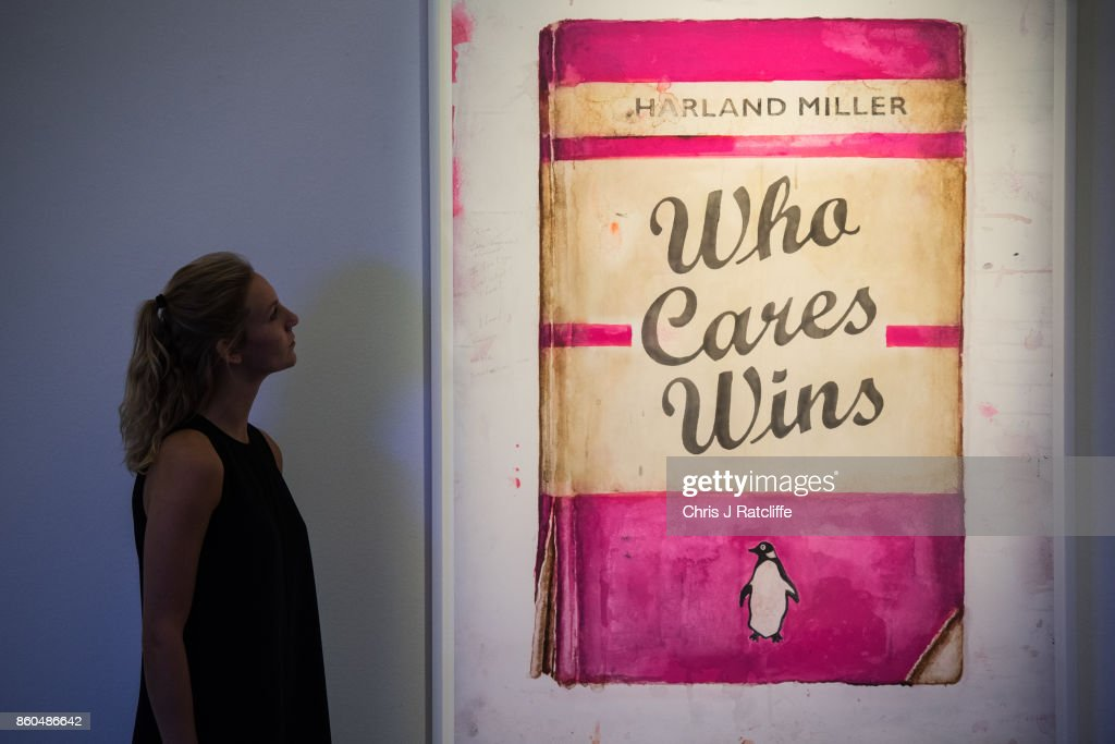 A woman poses for photographs next to Who Cares Wins by Harland Miller, estimated at £20,000-£25,000, during an Art for Grenfell press call at Sotheby's Art for Grenfell preview on October 12, 2017 in London, United Kingdom. The 'Art for Grenfell' auction will take place on October 16 2017 and includes work by contemporary artists.