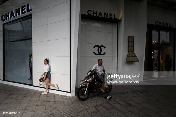 Woman poses for photographs outside a store of the luxury brand Chanel in Ho Chi Minh City on June 29, 2020 as a motorcycle-taxi driver looks on.