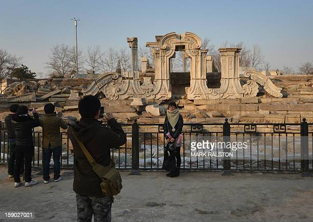 A woman poses for photos at the ruins of the historic Jesuit designed Yuanying Guan at the Old Summer Palace in Beijing on January 6 2013 The Old...