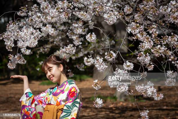 Woman poses for photos during the cherry blossom bloom on March 23, 2021 in Tokyo, Japan. On March 14, the Japan Meteorological Corporation declared...