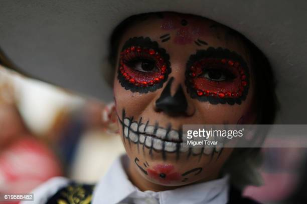 A woman poses for pictures wearing Catrina makeup as part of the Day of the Dead celebrations at Mexico City's Zocalo main square on October 31 2016...
