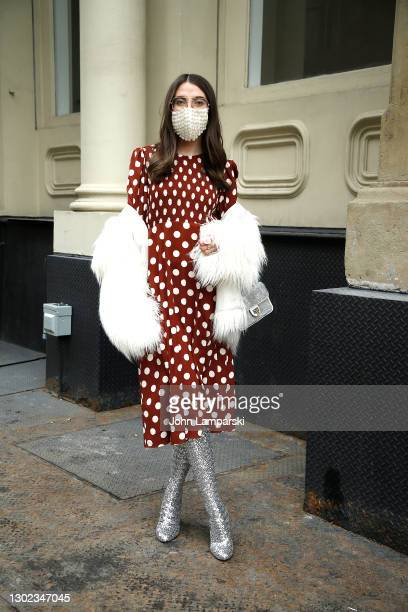 Woman poses in a Rag and Bone coat over Zara dress wearing boots by Dolce and Gabbana, bag by Nina and a protective mask by Akira in Tribeca on...