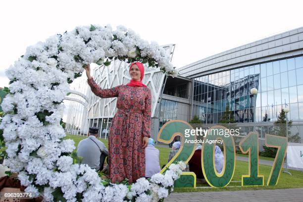 A woman poses in front of a crescent sign during the fifth Republican Iftar Dinner organized within the Muslims' fasting month of Ramadan at the...