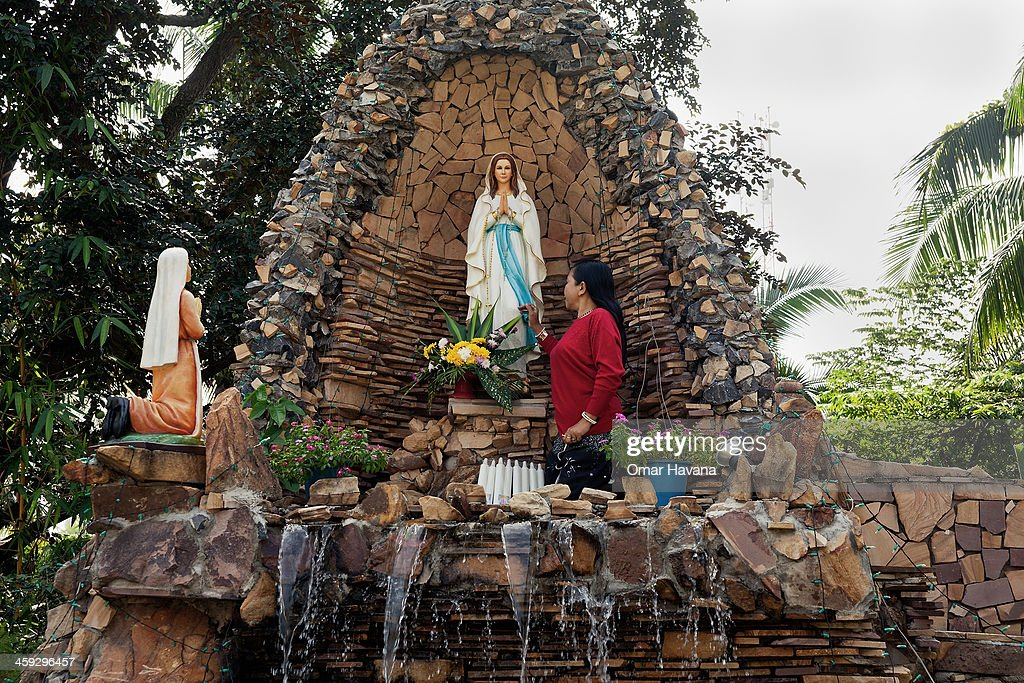 A woman poses in front of a statue of the Virgin Mary on December 25, 2013 in Battambang, Cambodia. The parish at Battambang dates back to 1790 when the Catholic community first arrived. Now they serve around 1000 Catholics and 600 families.