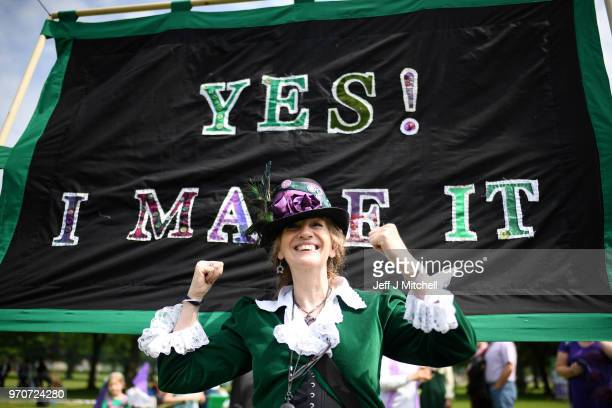 A woman poses in front of a 'Yes I Make It' banner as marchers gather on The Meadows ahead of Processions 2018 to mark 100 years since women won the...