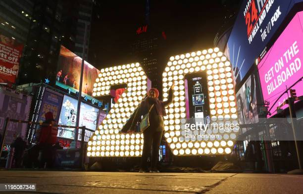 A woman poses in front of the number 20 sign that will be installed on top of the building in the background for the New Yearu2019s Eve Ball drop in...