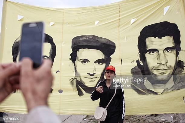 Woman poses in front of the poster of Turkish revolutonaries Deniz Gezmis, Huseyin Inan and Yusuf Aslan in Istanbul's Bakirkoy district during May...