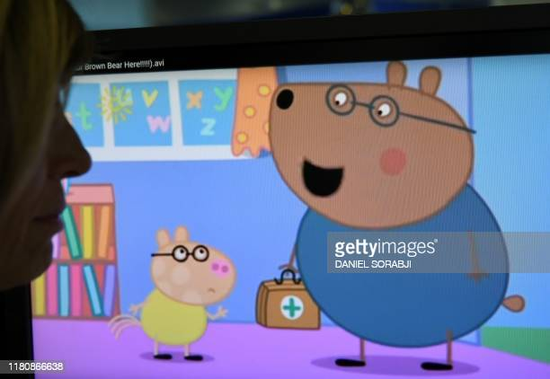 A woman poses in London on December 12 2017 looking at a screen showing an episode of British animated series Peppa Pig involving the character Dr...