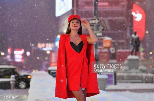 Woman poses in the snow at Times Square during a winter storm on February 1, 2021 in New York City. - A powerful winter storm is set to dump feet of...