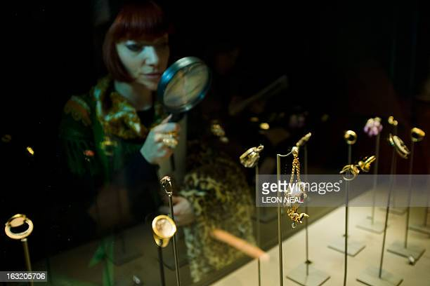 A woman poses looking at some of the items of jewellery on show at the Treasures of the Royal Courts Tudors Stuarts and the Russian Tsars exhibition...
