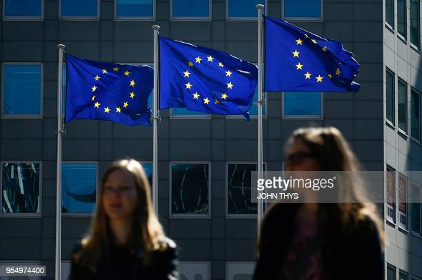 A woman poses near European flags as she visits she EU headquarters during the open day at the EU headquarters in Brussels on May 5 2018