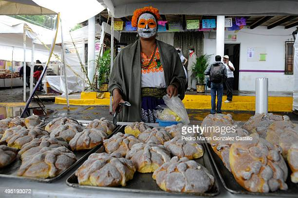 A woman poses near the traditional pan de muerto during the Day of The Dead at Panteon Municipal on October 31 2015 in Capula Mexico The threeday...