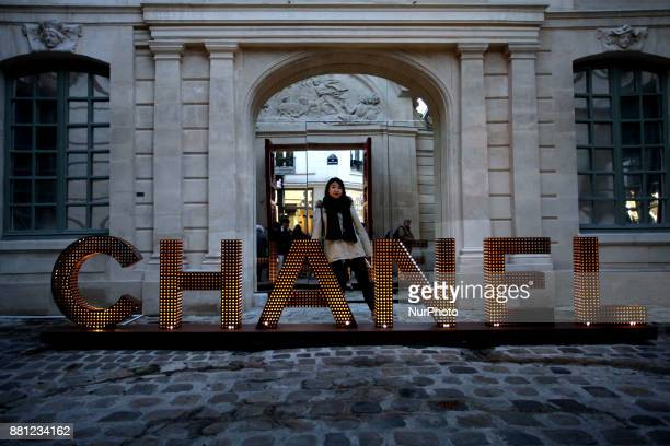 A woman poses next to a Chanel sign in Paris France on November 25 2017