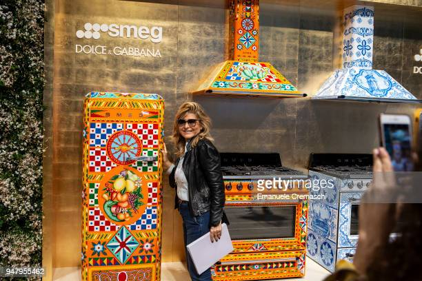A woman poses next to a Dolce Gabbana for Smeg limited edition refrigerator at the SMEG display stand during the Salone Internazionale del Mobile at...