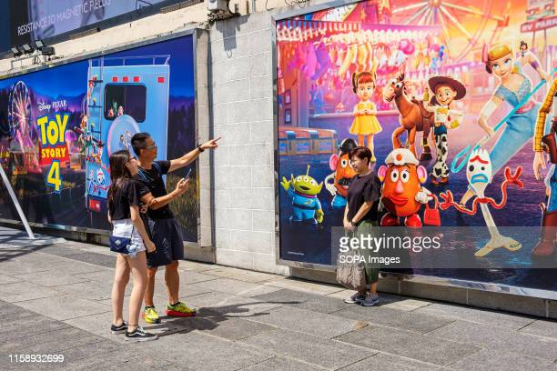 A woman poses next to an image of Potato Head Bo Peep Jessie Squeeze Toy Aliens Forky and Gabby Gabby during the Carnival Toy Story 4 is celebrated...