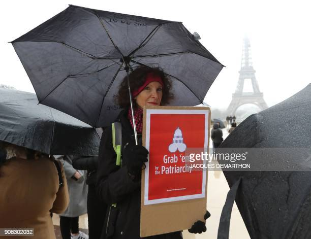 A woman poses next to the Eiffel tower as she holds a sign on the Trocadero esplanade in Paris on January 21 2018 during a women's march organized as...