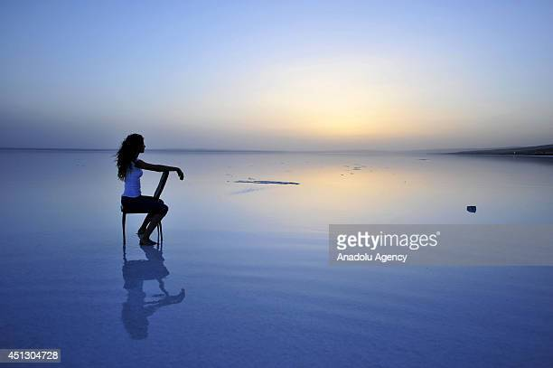 A woman poses on Lake Tuz the second largest salted lake of Turkey at sunset on June 27 2014