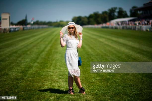 Woman poses prior to the start of the Prix de Diane, a 2,100-meters flat horse race, on June 18, 2017 at the Chantilly hippodrome, north of Paris. /...