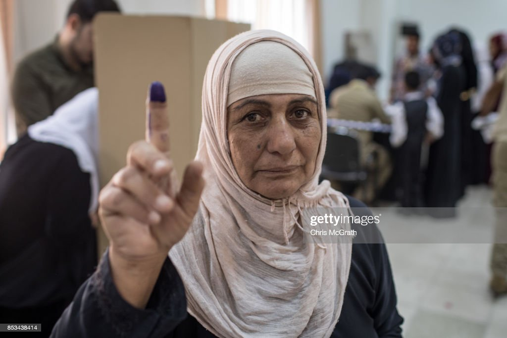 A woman poses showing off her finger provng that she cast her referendum vote at a voting station on September 25, 2017 in Erbil, Iraq. Despite strong objection from neighboring countries and the Iraqi government. Some five million Kurds took to the polls today across three provinces in the historic independence referendum.