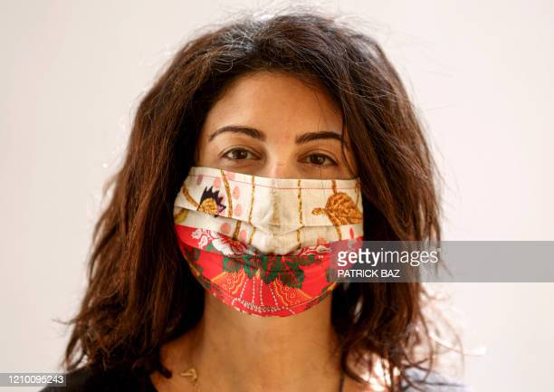 A woman poses while wearing an organic silk face mask produced by a local Lebanese fashion studio in the capital Beirut on April 15 2020 At a time...