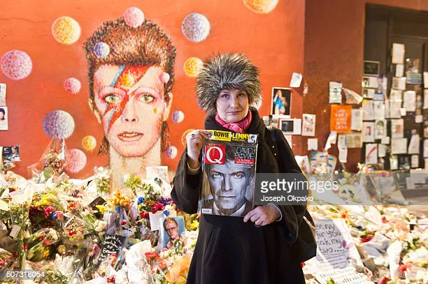 A woman poses with a copy of Q magazine near the impromptu shrine of English singer songwriter David Bowie opposite the Brixton tube station on...