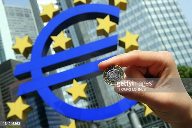 A woman poses with a Euro coin in front of the giant symbol of the European Union's currency the Euro in the background outside the headquarters of...