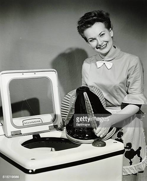 "Woman poses with a ""Kelvinator"" washing machine. Undated photograph, circa 1950's."