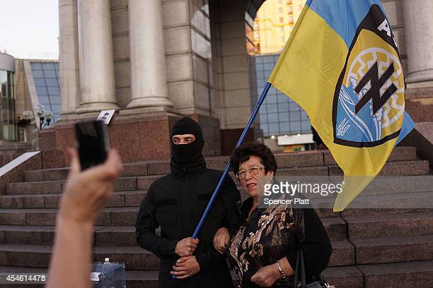 Woman poses with a member of the Azov Battalion, a far-right group of militant activists, stand in Independence Square, or Maidan Square, on...