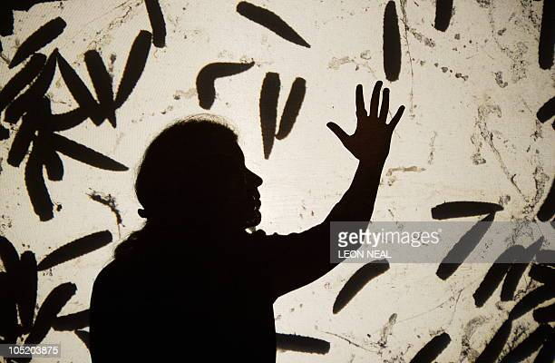 A woman poses with a projection of live maggots on a screen in Paul Insect's Maggot Planet installation at the Hell's Half Acre exhibition at the Old...