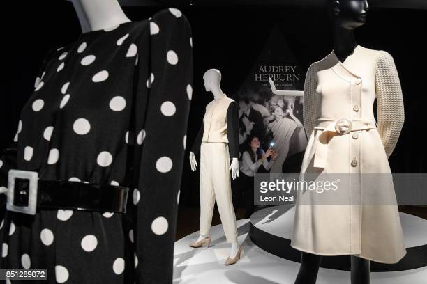 A woman poses with a selection of dresses during a preview of items from the sale of actrees Audrey Hepburn's personal collection at Christies on...