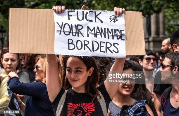 A woman poses with a sign with the text 'fuck your manmade borders' More than 3000 people have demonstrated in the center of Barcelona to support...