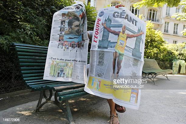 A woman poses with a special edition of French sport daily l'Equipe on July 26 which front page reads 'Giant' on July 26 2012 in Paris The paper...