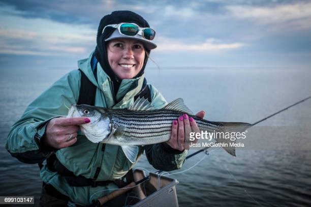A woman poses with a striped bass she caught while fly fishing on Marthas Vineyard.
